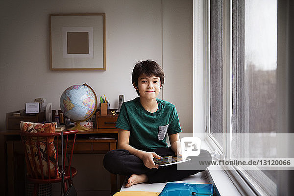 Portrait of boy holding tablet and sitting on table by window at home
