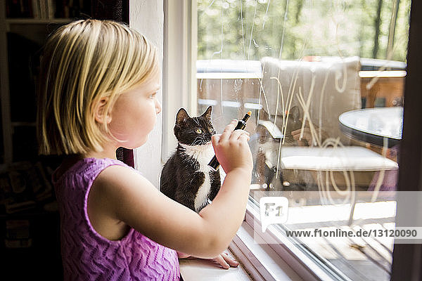 Side view of girl writing on window glass while standing by kitten at home