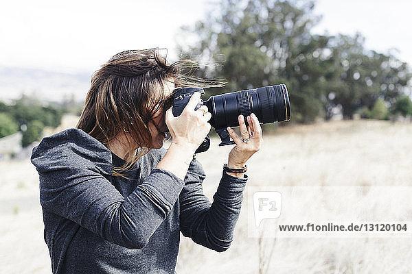 Frau fotografiert mit Kamera  während sie auf dem Feld steht