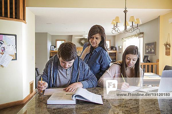 Mutter schaut Kindern zu Hause beim Lernen auf dem Tisch zu