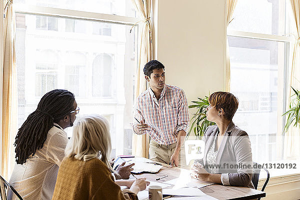 Businessman giving presentation to colleagues in office