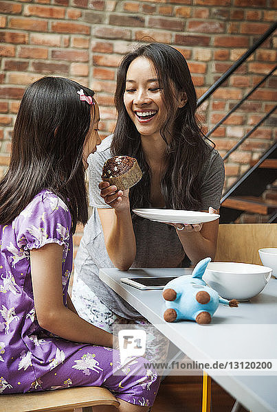 Mother feeding cup cake to daughter while sitting at table
