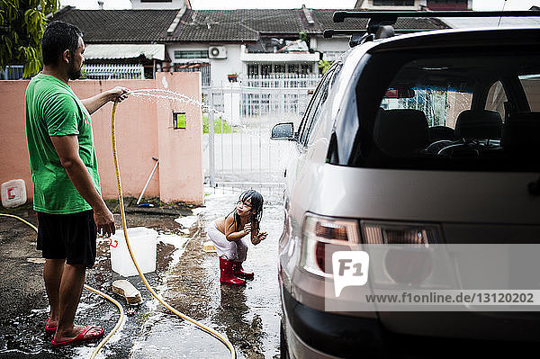 Playful Boy looking at father cleaning car in yard