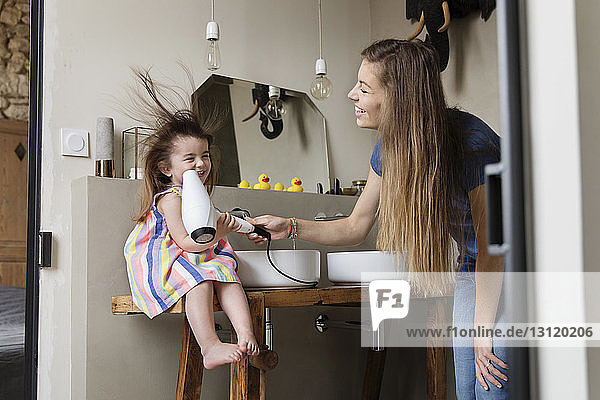 Low angle view of mother drying happy daughter's hair sitting on bathroom sink at home