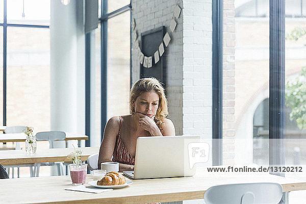 Frau mit Hand am Kinn mit Laptop-Computer  während sie im Café sitzt