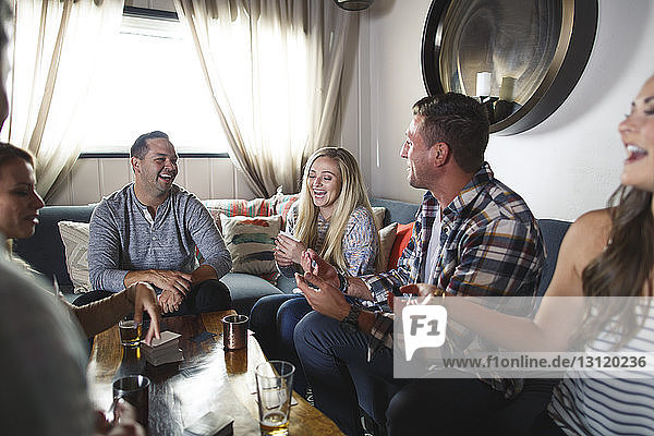 Cheerful friends playing card game at home