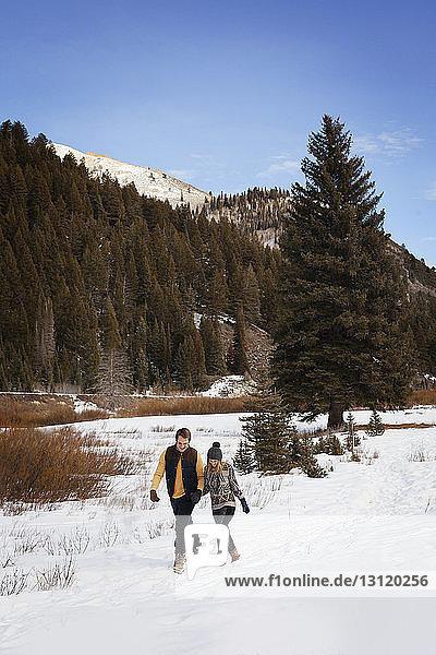 Junges Paar geht auf schneebedecktem Land gegen den Himmel