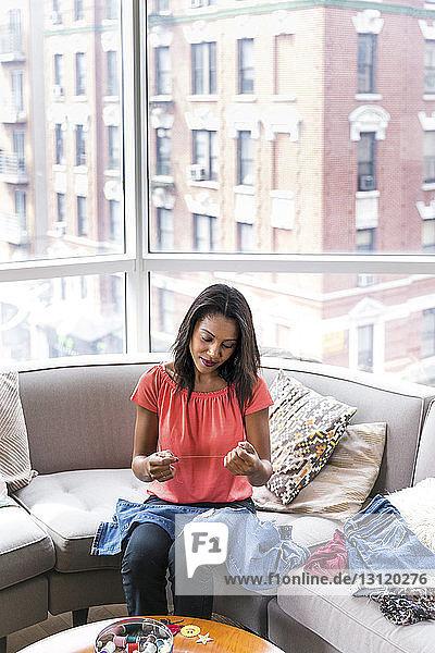 Hochwinkelansicht einer Frau  die einen Faden hält  während sie zu Hause auf dem Sofa am Fenster sitzt