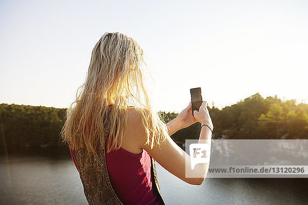 Rear view of young woman photographing nature through smart phone