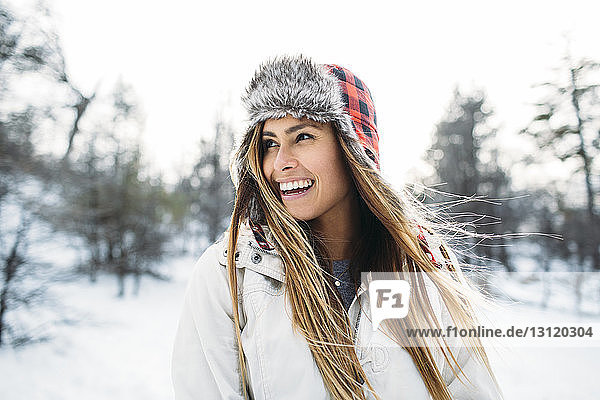 Close-up of cheerful woman wearing fur hat standing at snow covered field