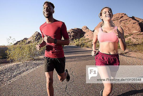 Glückliche Wanderer rennen auf der Straße gegen den klaren blauen Himmel