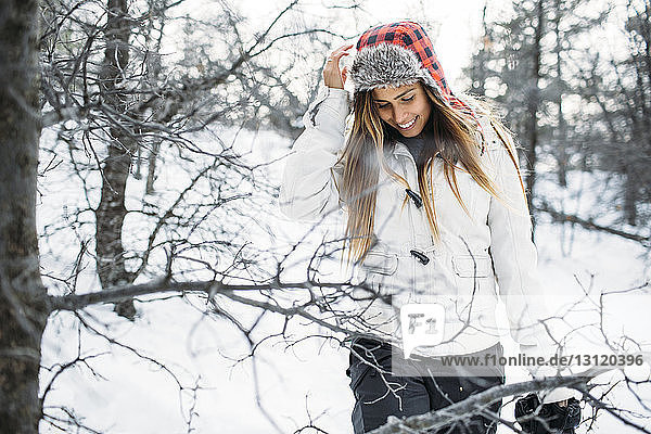 Frontansicht einer lächelnden Frau mit Pelzmütze  die auf einem schneebedeckten Feld steht