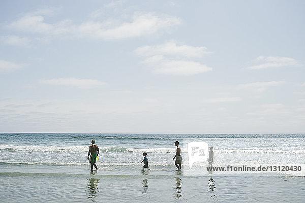Family walking in sea against sky