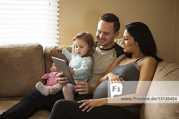 Familie schaut auf Tablet-Computer  während sie zu Hause auf dem Sofa sitzt