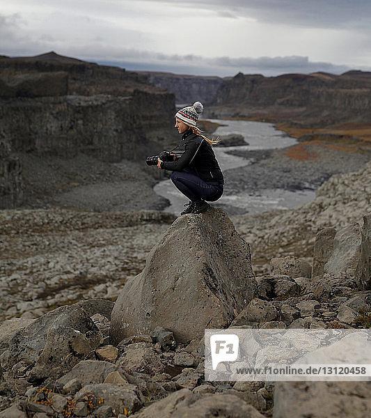 Seitenansicht einer Wanderin  die eine Kamera hält  während sie auf einem Felsen kauert