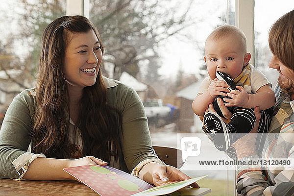 Glückliche Eltern mit Baby und Bilderbuch am heimischen Tisch