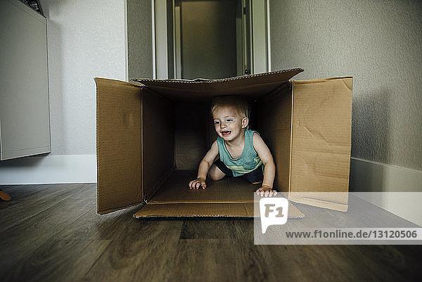 Kleiner Junge spielt zu Hause in Pappkarton