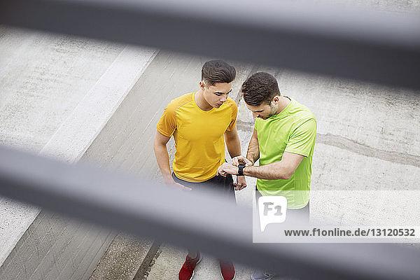 Hochwinkelaufnahme von männlichen Athleten  die die Zeit auf dem Fußweg am Parkplatz kontrollieren