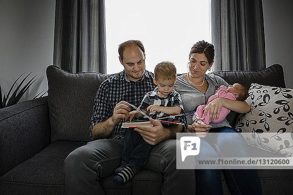 Parents with children looking photo album while sitting on sofa at home