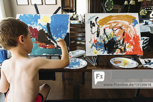 Rear view of boy painting at home