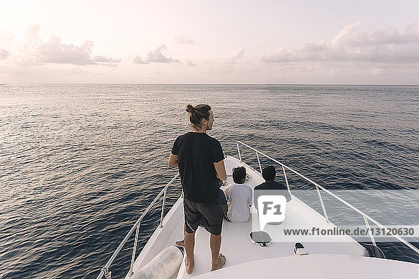 Rear view of male friends traveling in yacht on sea against sky during sunset