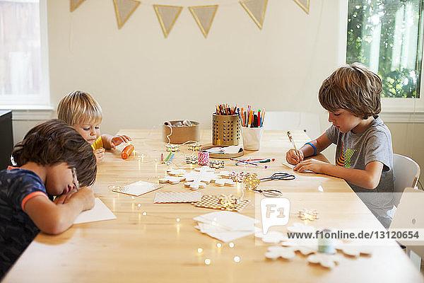 Geschwister  die am Tisch sitzend handwerkliche Dekorationen herstellen