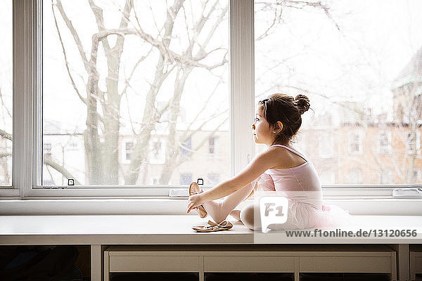 Girl sitting on table and wearing ballet shoes against window