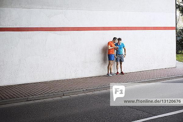Männliche Athleten in voller Länge  die die Zeit auf dem Fussweg auf der Strasse kontrollieren