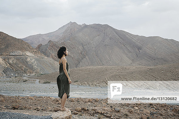 Side view of woman looking away while standing on rock against sky