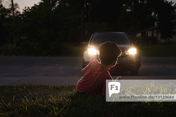 Boy relaxing on grassy field while looking at illuminated car at dusk