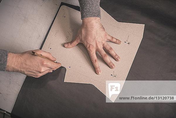 zugeschnittene Hände eines Schuhmachers  der Leder mit der Ahle auf der Werkbank in der Werkstatt schneidet zugeschnittene Hände eines Schuhmachers, der Leder mit der Ahle auf der Werkbank in der Werkstatt schneidet