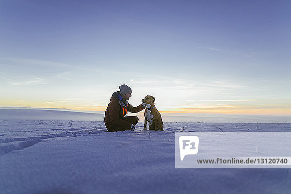 Hiker petting dog while sitting on snowy field against sky during sunset
