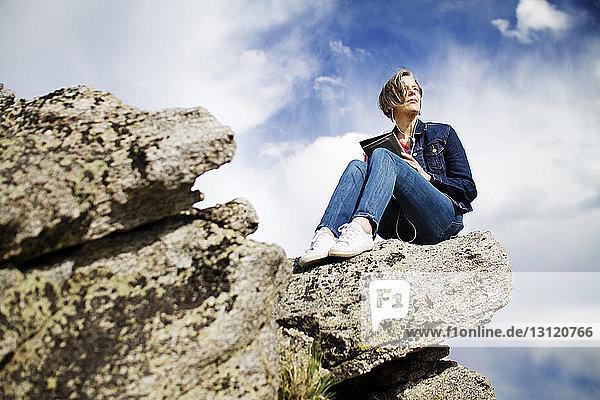 Niedrigwinkelansicht einer Frau  die Musik hört  während sie auf einem Felsen vor bewölktem Himmel sitzt