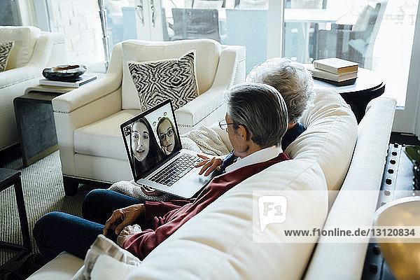 Älteres Ehepaar Videokonferenzen mit Enkelinnen über Laptop-Computer  während es auf dem Sofa im Wohnzimmer sitzt