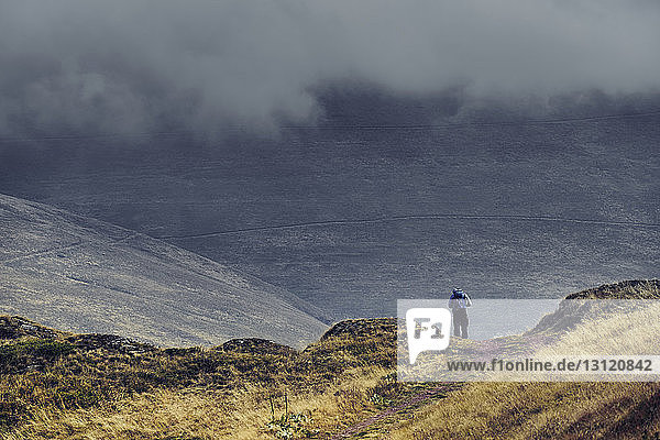 Rear view of man with backpack standing on Balkan Mountains against cloudy sky