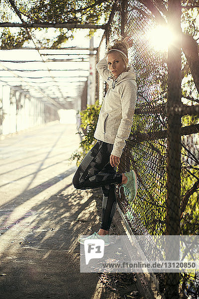 Portrait of confident woman leaning against fence on sunny day