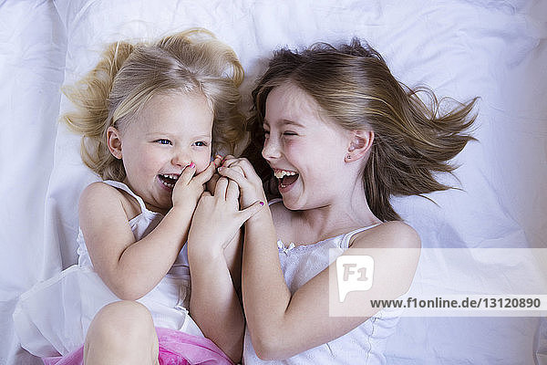 High angle view of happy sisters lying on bed at home