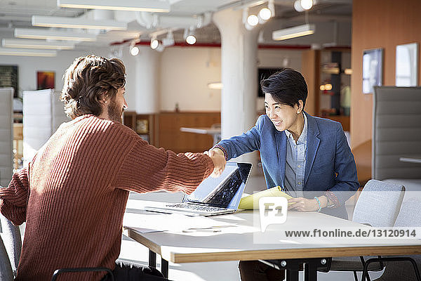 Geschäftsleute beim Händeschütteln am Tisch im Büro