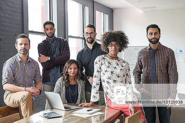Portrait of business people at desk in office