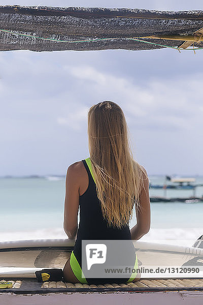 Rear view of woman with surfboard sitting at beach against sky