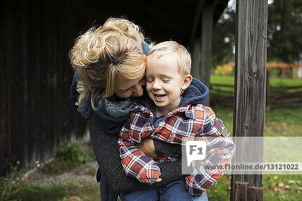 Verspielte Mutter umarmt Sohn auf dem Bauernhof