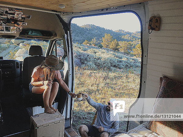 High angle view of couple toasting drinks while sitting in motor home at forest