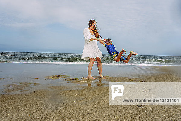 Playful mother swinging son on shore at beach against sky