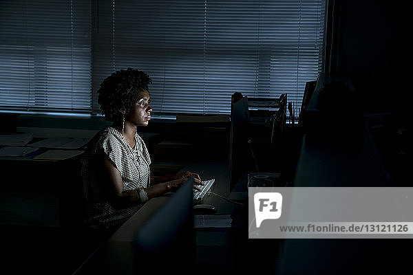 Side view of businesswoman working on desktop computer at desk in office