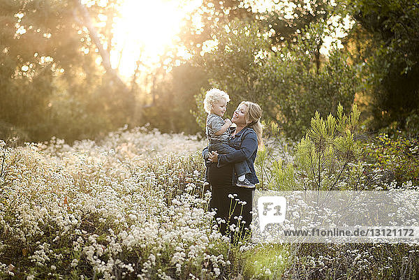 Smiling pregnant woman carrying son while standing amidst plants