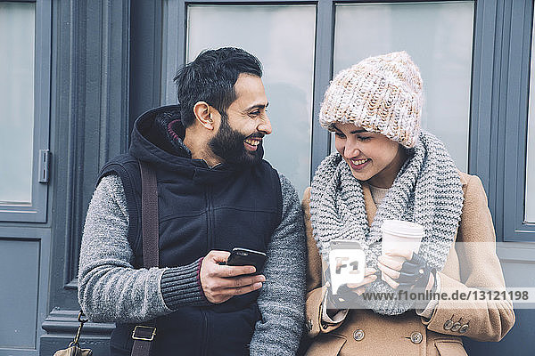 Happy man showing mobile phone to girlfriend while leaning by building