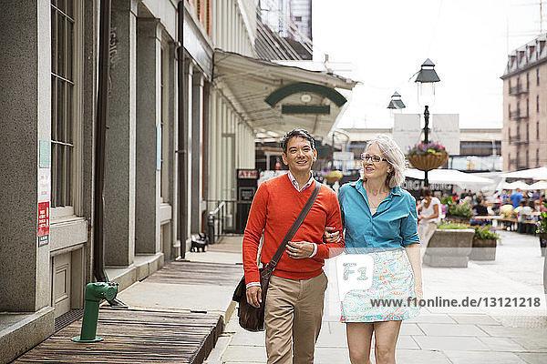 Mature couple walking on sidewalk in city