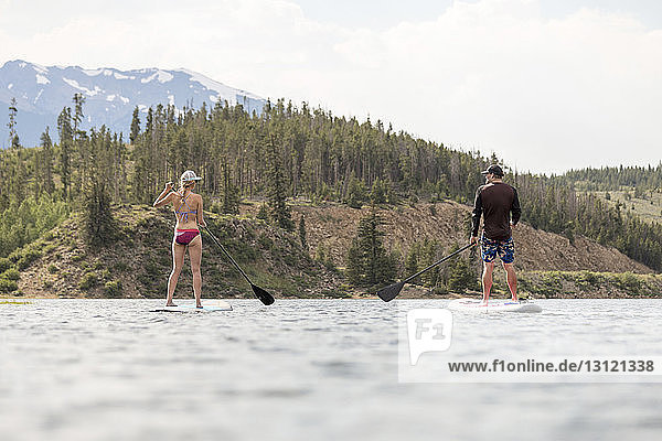 Rear view of friends paddleboarding on lake against mountains