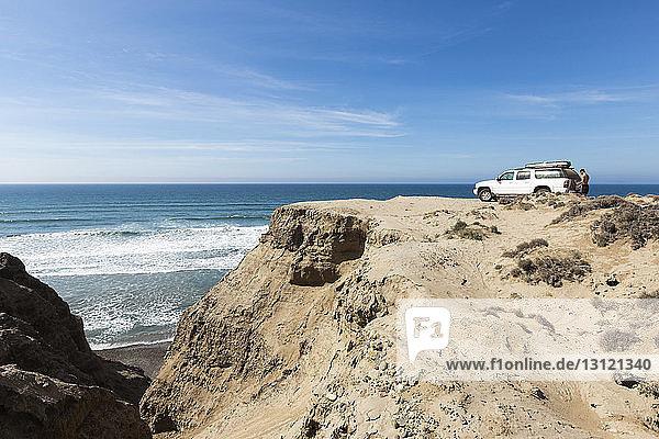 Seitenansicht eines Mannes ohne Hemd  der an einem Pickup auf einer Klippe gegen das Meer steht
