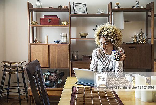 Lächelnde Frau benutzt Laptop  während sie im Haus eine Kaffeetasse am Tisch hält